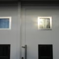 Aluminium Haustür mit Edelstahl-Applikationen und Stoßgriff