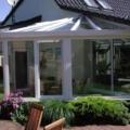 Aluminium Wohnwintergarten abgewalmtes Dach & 90 Grad Ecke & Unterbauelemente Balkontür und Dreh Kipp Fenster & Kunststoff Haustür & Dachfenster Farbe RAL 9016 Weiß & Dachverglasung als 2-Fach Verglasung VSG 10 mm montiert auf einen Klinkersockel