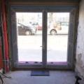 Aluminium Ladentür mit Glas 2-Flügelig & Barrierefreie Magnet-Nullschwellen (nur 4 mm Luft zwischen Türflügel unten und Nullschwelle) & Wasserabläufe für Anschluss an Drainage oder Regenwasser Ablauf